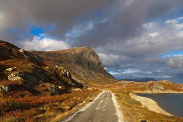 Autumn colours along Bygdisheimvegen with the mountain Synshorn in the background. The gravel road is flat and easy to cycle on.