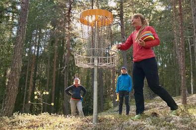 Three disc golf players in the forest close to Valdres Storhall in Leira.