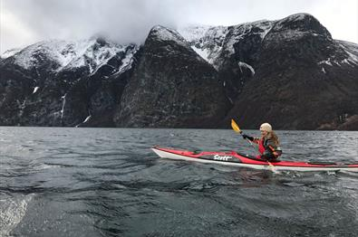 Girl in a red kayak og a fjord with black steep rock faces covered by a thin snow layer in the background.