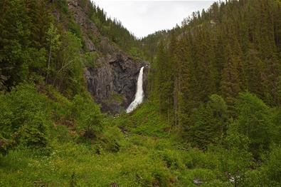 The waterfall Juvfossen falls over a rocky cliff surrounded by lush green vegetation.