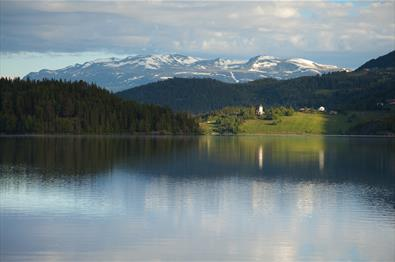 Lake Slidrefjorden seen from the rest area along road E16 near Lomen with the Lomen church and the mountain massif of Vennisfjellet in the background.