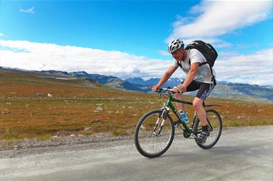 Cyclist on Slettefjellvegen with Jotunheimen's peaks in the background.