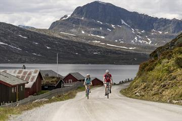 Cycling along Jotunheimvegen, a part of the Mjølkevegen Cycling Route, with the mountain of Bitihorn in the background.