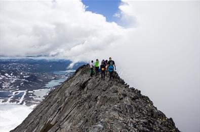 Narrow mountain ridge with hikers. In the background far below the summit some pale green glacier lakes can be seen. A cloud is drifting in towards th