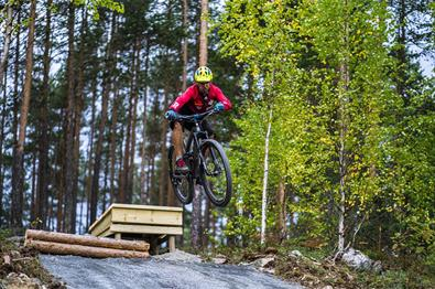 A cyclist jumping over an obstacle in  the terrain cycling area at Leira