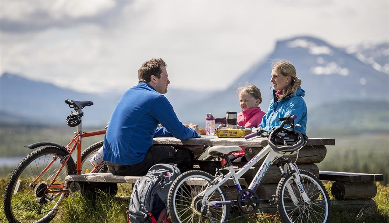 A family on a bicycle trip takes a break at a rest area with picknick table. Mountains in the background.